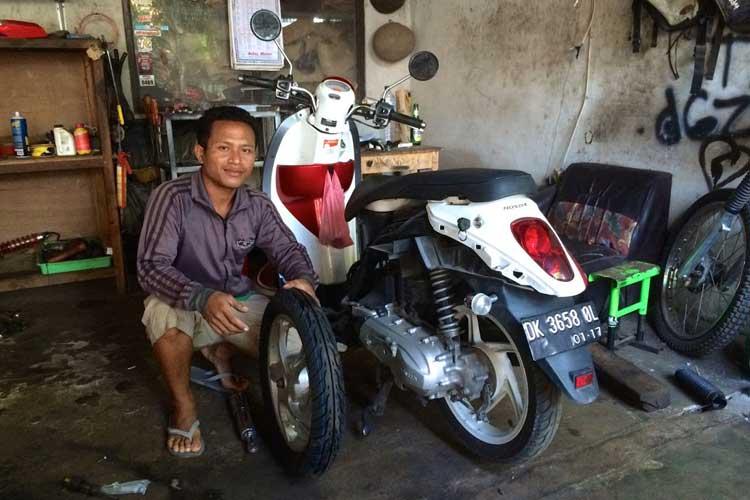 Gede poserer foran min sykkel på verkstedet, som forresten er et sted hvor det bygger om motorsykkeler for Trail...
